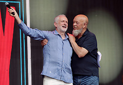 Labour leader Jeremy Corbyn (left) and event Organiser Michael Eavis speak to the crowd from the Pyramid stage at Glastonbury Festival, at Worthy Farm in Somerset.