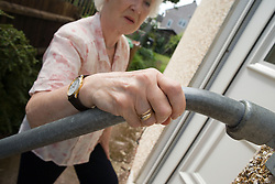 Woman, using grab handrails to help her up the steps outside her front door,