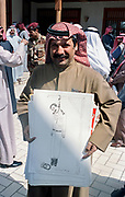 A Kuwaiti artist smiles as he shows off anti-Iraq drawings he plans on presenting the Emir of Kuwait Sheikh Jaber al-Ahmad al-Sabah following the liberation March 16, 1991 in Kuwait City, Kuwait. After four days of fighting, all Iraqi troops were expelled from Kuwait, ending a nearly seven-month occupation of Kuwait by Iraq.