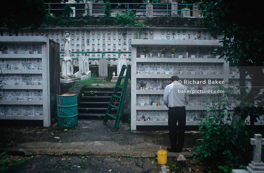 While still a British colony, a 1990s Chinese man stands in prayer near family vaults in the Muslim and Catholic cemetery, on 21st April 1995, in Hong Kong, China.