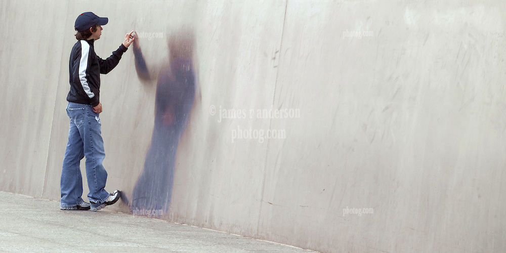 A teenager touching, and his reflection on, the stainless steel of the base of Saint Louis Gateway Arch. Wide version.