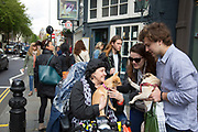 A woman taking her chihuahua out for a 'walk' on her mobility scooter on the Kings Road in Chelsea stops another dog owner with a pug, and the two dogs get to meet each other. In a selected few boroughs of West London, wealth has changed over the last couple of decades. Traditionally wealthy parts of town, have developed into new affluent playgrounds of the super rich. With influxes of foreign money in particular from the Middle-East. The UK capital is home to more multimillionaires than any other city in the world according to recent figures. Boasting a staggering 4,224 'ultra-high net worth' residents - people with a net worth of more than $30million, or £19.2million.. London, England, UK.