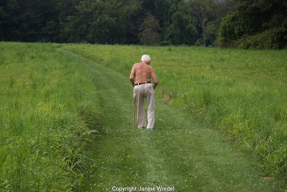 Older man walking across green field passage to future