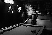 """NAIROBI, KENYA - AUGUST 18, 2011: Idle youth in Kisumundogo village play """"Whiteless,"""" a popular billiards game in Kenya, at the former Railbreeze Pub. Once an active bar and restaurant, Railbreeze is now an empty hut in which Kenyan youth play pool to pass the time. <br /> <br /> Various grassroots initiatives led by youth have begun to improve the quality of life for those living in the direst of conditions, and young people of different tribes are using gardening, waste removal, education and athletics to encourage their peers toward a self-respecting and self-sustaining community. Termed """"youth groups"""" on the street, these initiatives could represent the future of long-term socioeconomic development in Kenya while laying the groundwork for a more peaceful election in 2013. During the post-election violence of 2007 and 2008, impoverished youth in Kenya were routinely bribed by the nation's political elite to carry out acts of violence in their communities. Idleness among the youth, combined with the nation's history of tribal rivalries, were cited as a key factors to the violence, culminating in the deaths of over 1,200 Kenyans and the displacement of over 600,000. Since the violence, many youth have begun to seize active roles in the reform of their nation. In 2010 United States Ambassador Michael Ranneberger said he sensed """"a sea change of attitude"""" among youths, """"a tidal wave below the surface. The youth have woken up."""""""