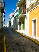 Man in a doorway, balconies and colorful building facade, Old San Juan/Viejo San Juan.
