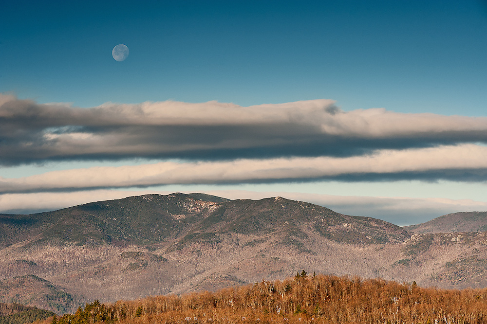 Adirondacks, NY.<br /> Clouds hung in rows above the High Peaks, but the setting moon manged to hover above them for a little while, as the sunrise lit the nearer foothills with some golden light.