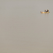 A sampan, or small wooden fishing boat, with two fishermen on the Perfume River in Hue, Vietnam.