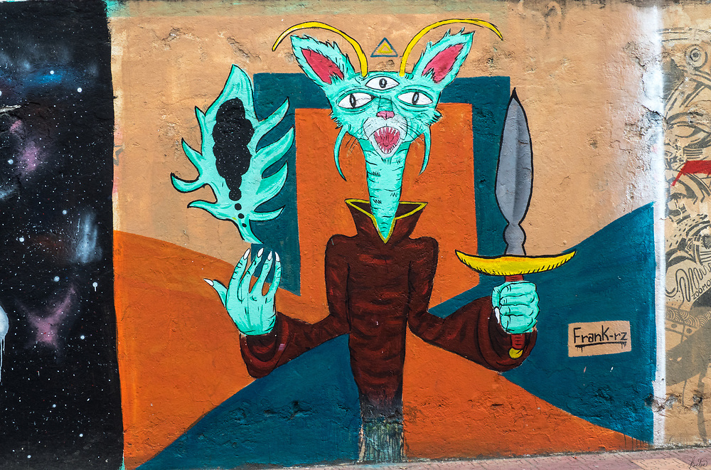 A street mural of a cat with a third eye and a sword in Ecuador.