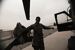 """Exhausted Flight medic Stephen Montavon sheds his body armor at the completion of a mission. Scenes from the medical evacuations of wounded Americans, Canadians, and Afghan civilians and soldiers being flown by Charlie Co. 6th Battalion 101st Aviation Regiment of the 101st Airborne Division. Charlie Co. - which flies under the call-sign """"Shadow Dustoff"""" - flies into rush the wounded to medical care out of bases scattered across Oruzgan, Kandahar, and Helmand Provinces in the Afghan south. These images were taken of missions flown out of Kandahar Airfield in Kandahar Province and Camp Dwyer in Helmand Province."""