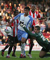 Photo: Frances Leader.<br />Brentford v Swindon Town. Coca Cola League 1.<br />15/10/2005.<br /><br />Brentford nearly score as Swindons's goalie Tom Heaton drops the ball in front of the gaol and grabs onto Jerel Ifil but the ball is cleared.