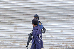 JOHANNESBURG, SOUTH AFRICA - APRIL 18: A man is escorted home by a SAPS officer during a South African Police Service (SAPS) Metro Police and Army supported patrol in Rockey Street, Yeoville. Random searchs and social distancing measures on April 18, 2020 in Johannesburg South Africa. Under pressure from a global pandemic. President Ramaphosa declared a 21 day national lockdown extended by another two weeks, mobilising goverment structures accross the nation to combat the rapidly spreading COVID-19 virus - the lockdown requires businesses to close and the public to stay at home during this period, unless part of approved essential services. (Photo by Dino Lloyd)