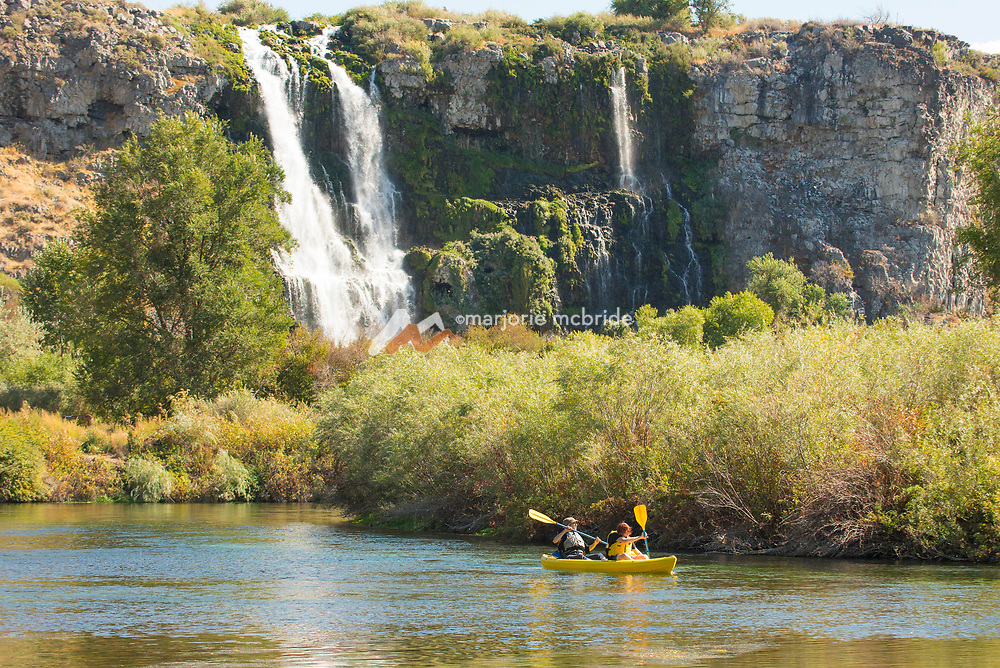 Two people kayaking under large beautiful waterfall during the Thousand Springs Art Festival at Ritter Island near Hagerman, Idaho.
