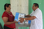 Elsa Ellis (left), BSCFA member from San Joaquin, receives a fan for her home from Ramón Aban, chairman of the BSCFA San Joaquin branch. Belize Sugar Cane Farmers Association (BSCFA). San Joaquin, Corozal, Belize. January 23, 2013.