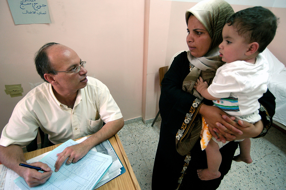 George Imseih, an ACT Alliance-supported physician working in the health center in the Ama'ri Refugee Camp in Ramallah, discusses a young patient's growth with its mother.