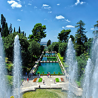Villa d'Este. Tivoli. Italy. View through spurting water from the fountain of Neptune of the magnificent landscaped and lush level gardens and fishponds at the Villa d Este in Tivoli.  Villa d'Este, renowned for its spectacular use of water, represents the quintessence of the Italian garden of the High Renaissance. It is a designated UNESCO world heritage site.