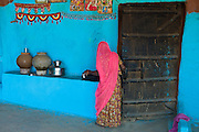Hindu woman in traditional blue painted home in Hindu Brahman high caste village of Dhudaly  in Rajasthan, India