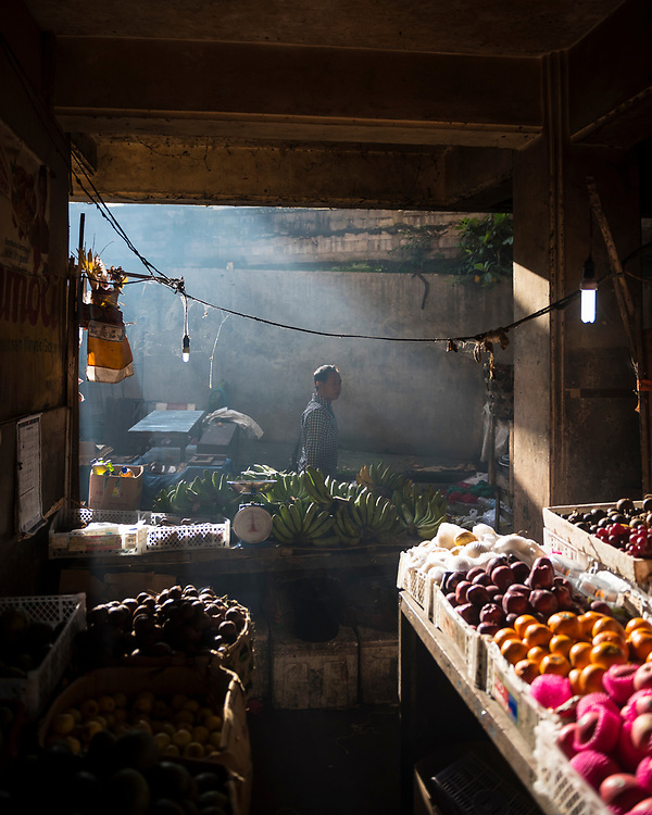 Bali, Indonesia - February 16, 2017: A man walks past a table of bananas and other fruit at the early morning market in Ubud, Bali, Indonesia