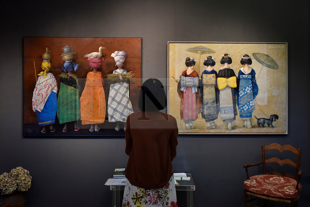 "© Licensed to London News Pictures. 27/06/2017. London, UK.  A visitor views (L to R) ""Niger"" and ""Osaka"" both by Manuel Lopez Herrera at The Arts & Antiques Fair taking place at Olympia in Kensington.  The event is the UK's largest and most established art and antiques fair and runs until 2 July.  Photo credit : Stephen Chung/LNP"