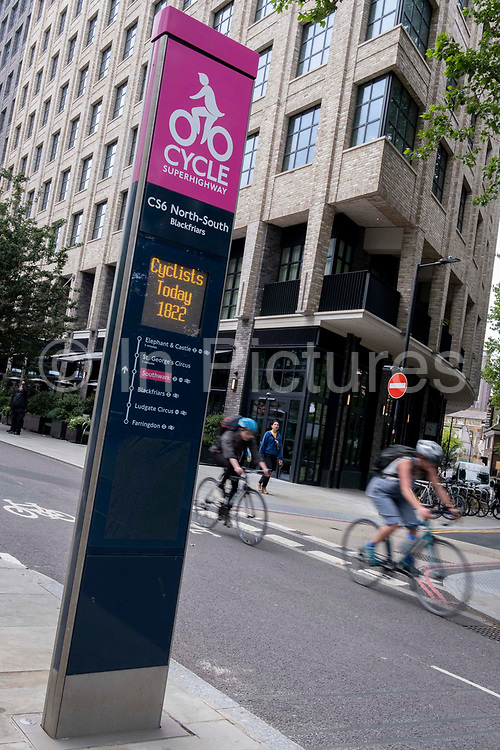 A cyclist rides past daily cycling statistics for the North-South CS6 Superhighway that allows commuters safe journeys south of Blackfriars Bridge, on 22nd June 2021, in London, England.