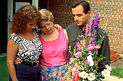 Spouses comforting mother ages 29 and 58 on death of her mom.  Beaver Dam Wisconsin USA