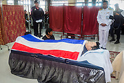 19 FEBRUARY 2014 - BANGKOK, THAILAND: Mourners at the bathing rites for Police Senior Sgt-Major Phianchai Pharawat, 45. Bathing rites are the first step in Buddhist funeral ritual. Phianchai was killed by anti-government protestors Tuesday during an altercation between protestors and police. Four people were killed and more than 60 hospitalized as a result of the fighting. Anti-government protestors aligned with Suthep Thaugsuban and the People's Democratic Reform Committee (PRDC) attacked police officers who tried to clear protestors out of sites they've occupied since January.    PHOTO BY JACK KURTZ