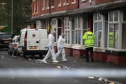 Forensics and a police officer at the scene in Claremont Road, Moss Side, Manchester, where ten people, including two children were taken to hospital after reports of gunshots at a street party.