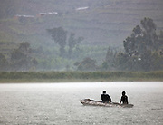 Local men paddling their small wooden canoe in pouring rains, South Western Uganda