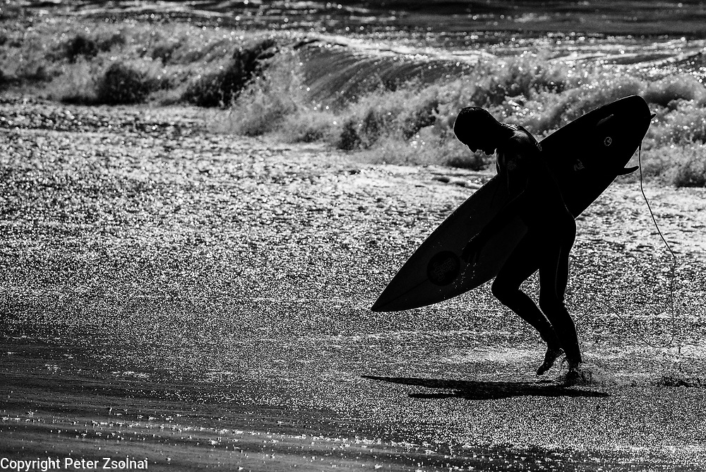 Surfer is coming out from the waves after a nice  riding a nice swell.