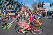 """Passing the Houses of Parliament, Westminster. The Tweed Run 2015 - it's 7th annual British public bicycle ride through London's historic streets, with a prerequisite that participants are dressed in their best tweed cycling attire. There are also plenty of handle bar moustaches, penny farthings and Union Jacks. """"Guests can expect a leisurely day cycling, stopping at some of London's most iconic landmarks to enjoy a spot of tea, a picnic in the park and finally a jolly good knees-up in a beautiful art-deco ballroom for the Tweed Run closing ceremony. Starting at Trafalgar Square, the cyclists then embarked on a 12 mile scenic ride through London, stopping at traditional spots."""