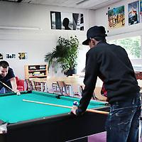Nederland, Amsterdam, 9 juli 2015.<br /> School2Care is een school speciaal voor de allermoeilijkste jongeren. Ze verblijven daar dagelijks van 8 tot 20 om alsnog een schoolcarriere te kunnen afmaken. Nu in de zomervakantie kan deze groep jongeren niet zo maar zes weken vakantie vieren. Te veel vrijheid zou hen terugduwen in een oud patroon. Daarom doen ze deze vakantie allerlei activiteiten.<br /> Op de foto coach Bouke Spigt en 1 vd jongeren tijdens een spelletje pool biljarten.<br /> <br /> <br /> <br /> Foto: Jean-Pierre Jans