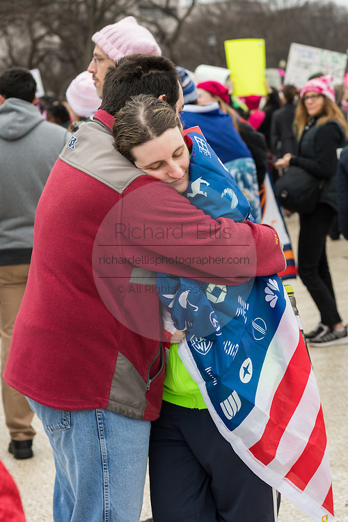 An exhausted couple embrace during the Women's March on Washington in protest to President Donald Trump January 21, 2017 in Washington, DC. More than 500,000 people crammed the National Mall in a peaceful and festival rally in a rebuke of the new president.