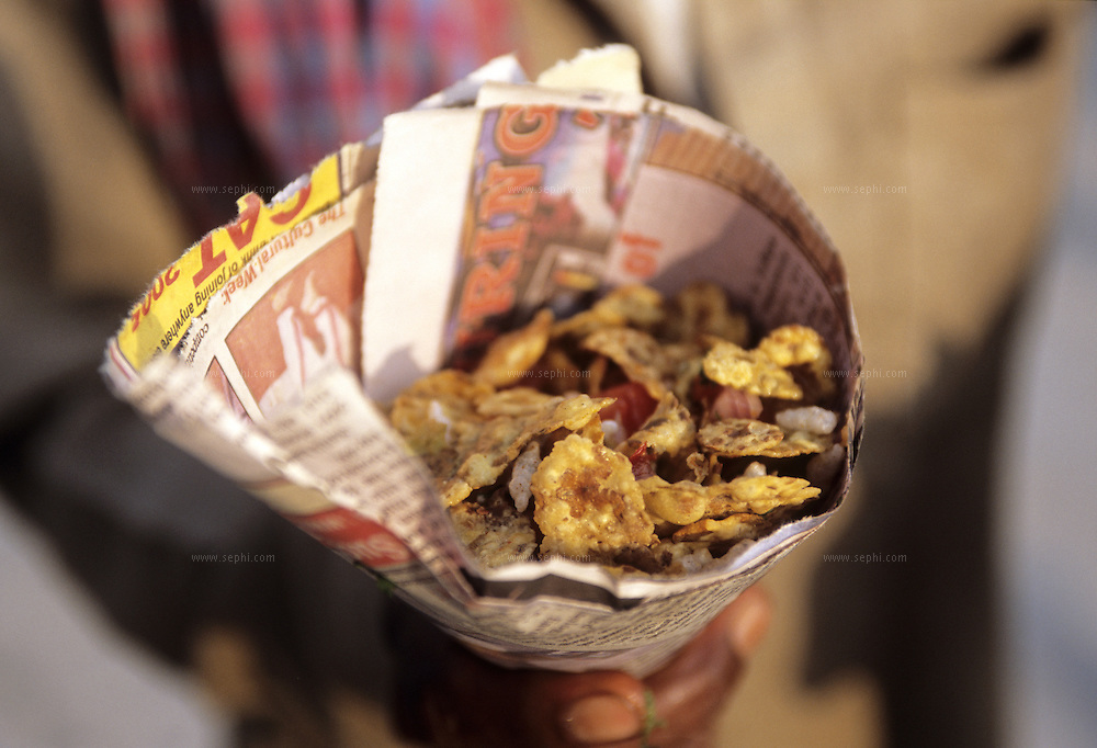 Chana Jor Garam - a mouthwatering Indian traditional snack made out of black gram !.Here an Indian man holding a serving rolled in a daily paper in Rishikesh, India