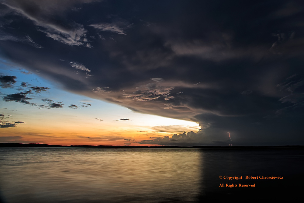 Cuban Storm Front: An evening's sunset is quickly overtaken with a dramatic storm front that not only darkens the sky, it splits the light cast upon the ocean, all the while lightning bolts highlight the distant horizon, Cienfuegos Cuba.