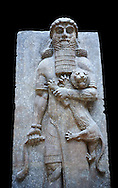 Stone relief sculptured panel of a Hero holding a lion. From the facade of the throne room,  Inv AO 19862 from Dur Sharrukin the palace of Assyrian king Sargon II at Khorsabad, 713-706 BC.  Louvre Museum Room 4 , Paris .<br /> <br /> If you prefer to buy from our ALAMY PHOTO LIBRARY  Collection visit : https://www.alamy.com/portfolio/paul-williams-funkystock/ancient-assyria-antiquities.html  Refine search by adding background colour, place, subject, museum etc into the LOWER SEARCH WITHIN GALLERY box to <br /> <br /> Visit our ANCIENT ASSYRIAN PHOTO COLLECTIONS for more photos to download or buy as wall art prints https://funkystock.photoshelter.com/gallery-collection/Ancient-Assyrian-Art-Artefacts-Antiquities-Historic-Sites-Pictures-Images-of/C0000cjRqQyJjLag