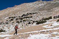 Female hiker hikers along partially snow covered Kearsarge Pass trail, Sierra Nevada Mountains, California
