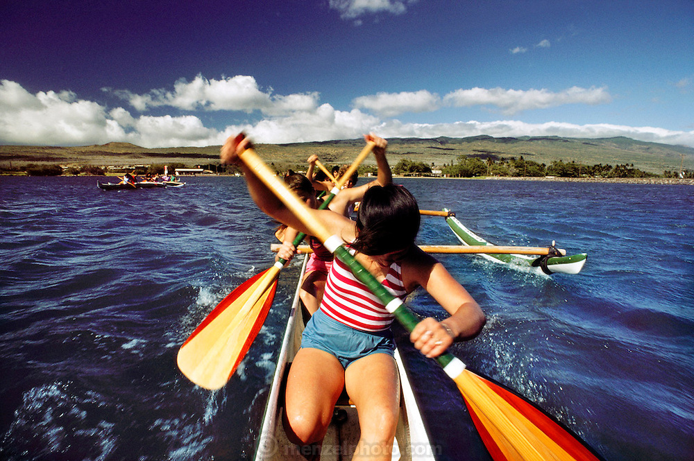 High school girls paddling an outrigger canoe. Kaunakakai, Molokai.