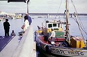 Fishing boats at quayside at Portimao, Algarve, Portugal, 1980s road bridge over the Rio Arade