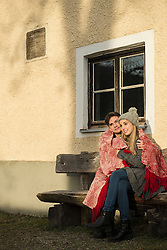 Young couple wrapped in a blanket sitting on bench during sunset, Munich, Bavaria, Germany