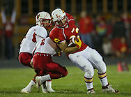 Marion's Trev Biery (33) tries to spin away from Maquoketa's Cory Wirth (1) on a run during the first half of the game between Maquoketa and Marion at Thomas Park Field in Marion on Friday, September 21, 2012.
