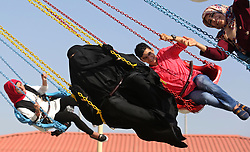 June 27, 2017 - Gaza City, Gaza Strip - Palestinians take a ride at an amusement park on the third day of Eid al-Fitr holiday which marks the end of the Muslim holy month of Ramadan. (Credit Image: © Ashraf Amra/APA Images via ZUMA Wire)