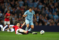 MANCHESTER, ENGLAND - Monday, April 30, 2012: Manchester City's Carlos Tevez in action against Manchester United's Park Ji-Sung during the Premiership match at the City of Manchester Stadium. (Pic by Chris Brunskill/Propaganda)