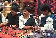 ECUADOR, MARKETS, CRAFTS Otavalo women buying necklaces