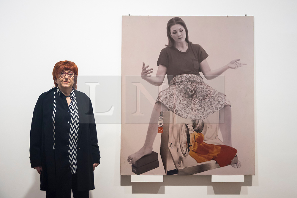 """© Licensed to London News Pictures. 28/11/2019. LONDON, UK. Austrian artist Valie Export poses with """"Die Geburtenmadonna"""", 1976, at the preview of her exhibition """"The 1980 Venice Biennale Works"""" at Galerie Thaddeus Ropac in Mayfair.  The exhibition comprises innovative multimedia installation from the 39th Venice Biennale and 17 large-scale photographs mounted on wooden panels from her important photographic series Body Configurations (1972–82).  The show runs 28 November to 25 January 2020.  Photo credit: Stephen Chung/LNP"""