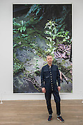 Wolfgang Tillmans with the Weed,2014 - Tate Modern's new exhibition. Highlights include: large scale photographic works printed especially for this exhibition, including the four-meter tall Weed 2014 and dramatic seascapes such as The State We're In, A 2015;   New 'text and table' sculptures including Time Mirrored 3 2017, on display to the public for the first time; and slide projection Book for Architects 2014. The show is at Tate Modern from 15 February to 11 June 2017.