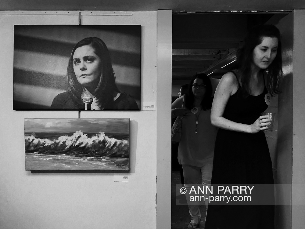 Manhasset, New York, U.S., June 2, 2019. Member of The Art Guild staff steps down into Library, with (at upper left) Ann Parry's photograph of Erica Lafferty Smegielski, during Reception for The Art Guild exhibition held at Elderfields Preserve. [Parry captured photograph of Smegielski in Port Washington, April 11, 2016.  Smegielski, who lost her mother Dawn Lafferty Hochsprungand, the Principal of Sandy Hook Elementary School in Newtown, CT, shared her personal story of loss of a loved one due to gun violence, during a discussion with Hillary Clinton and other activists on gun violence prevention.]