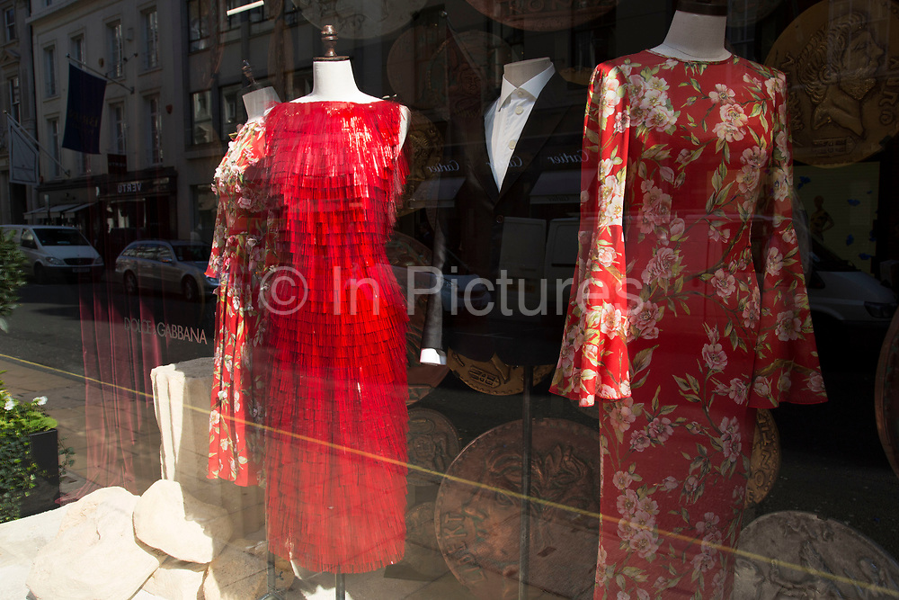 Red dresses for sale in the Dolce and Gabbana shop on Bond Street, London, UK. Dolce & Gabbana is an Italian luxury industry fashion house. The company was started by Italian designers Domenico Dolce and Stefano Gabbana. High end fashion on London's most exclusive shopping street.