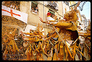 Women in gold costumes and masks dance in confetti as Christians @ Moors & Christians fest; Alcoy Spain