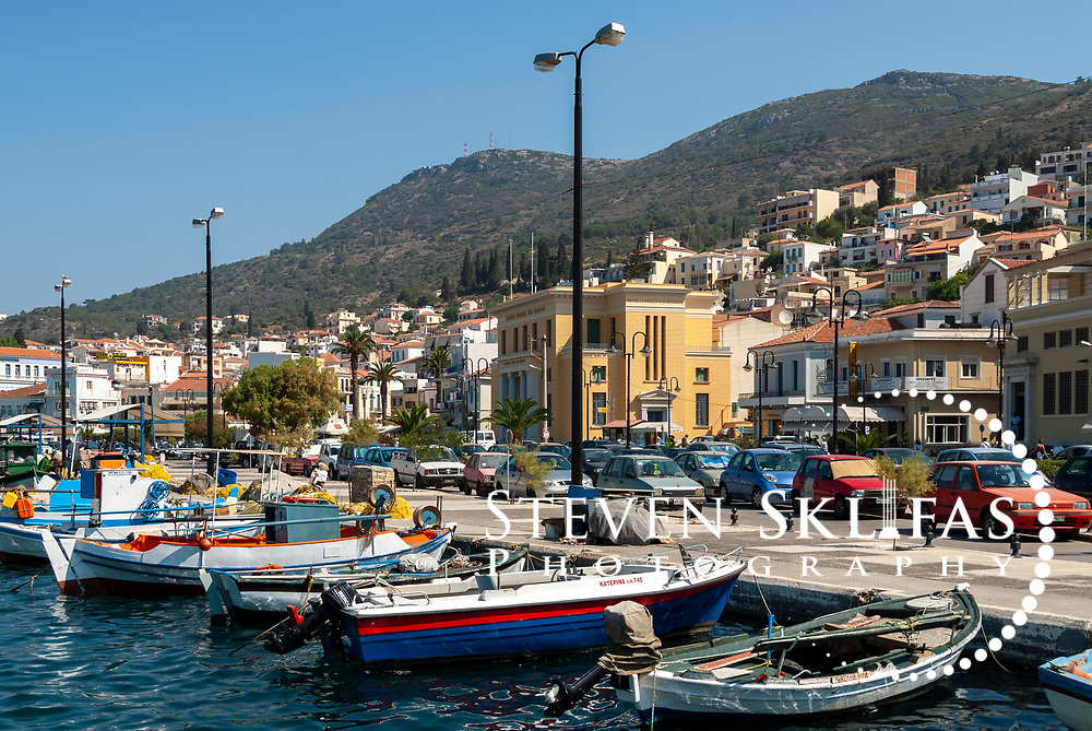 Samos. Greece. View of colourful boats docked in the harbour of Vathy or Samos town. Vathy is the Islands capital and largest town. The bustling palm tree lined waterfront of Vathy is adorned with neo-classical buildings many topped with red tiled roofs and the town rises steeply into wooded hills above.