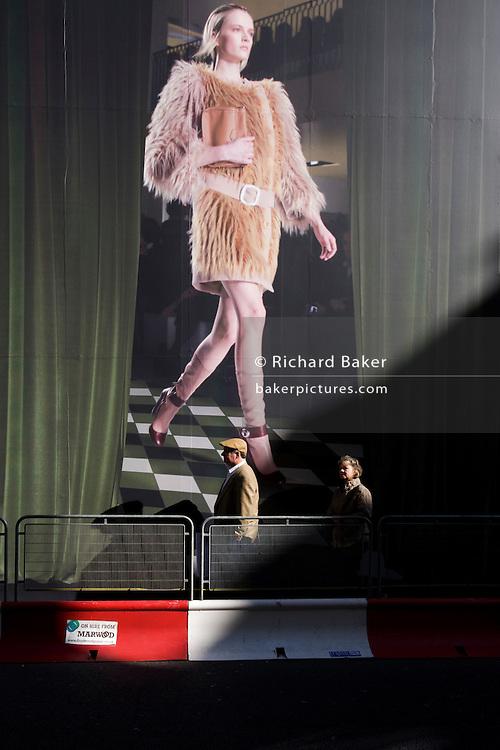 Two elderly pedestrians pass beneath a giant billboard featuring a catwalk model weaing haute couture.