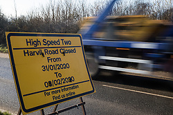 Harefield, UK. 21 January, 2020. A truck passes a sign announcing a closure of Harvil Road for work on the HS2 high-speed rail link expected to include the destruction of trees in the Colne Valley. 108 ancient woodlands are set to be destroyed by HS2.